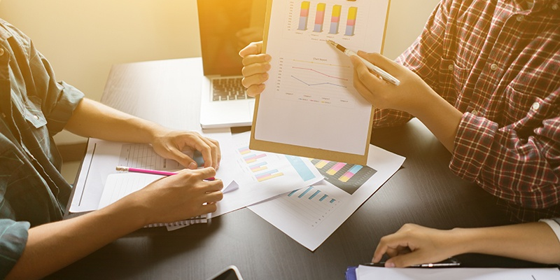 Businessman's hand showing diagram on financial report ,Analysis Brainstorming Business Working in office desk,show the results of their successful teamwork in loft office,vintage color,copy space